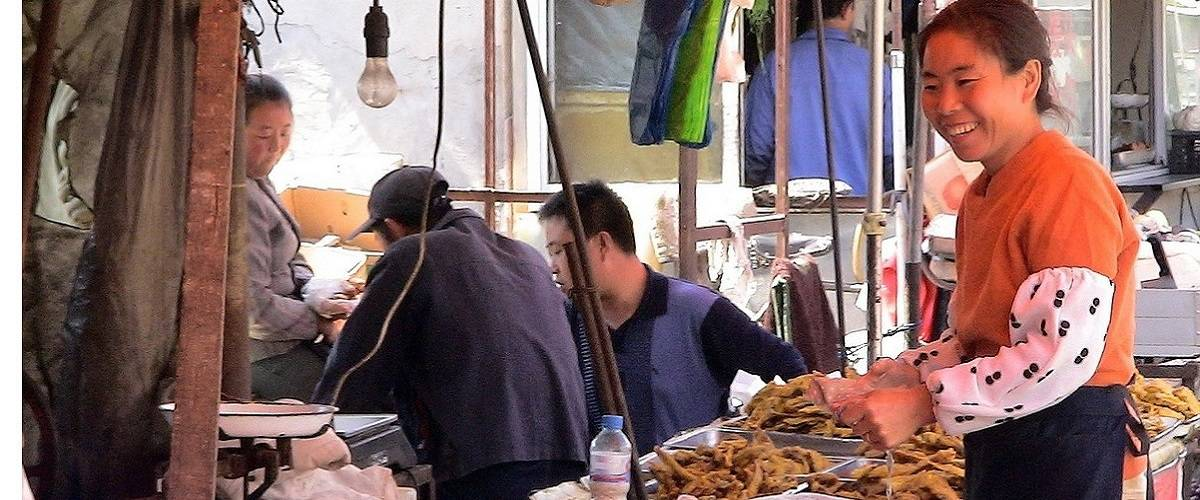 donna sorridente al mercato in Cina